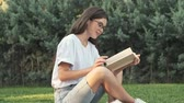 sedutor : Beautiful young girl wearing glasses is reading a book while sitting outside in the city park in the summer