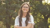トレンディー : Beautiful smiling girl wearing glasses is staying outside in the city park in the summer morning