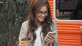 beautiful building : Focused positive fashionable young woman wearing glasses is using her smartphone while holding a paper cup of tea or coffee outside