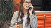 beautiful building : Focused positive fashionable young woman wearing glasses is having a phone call while holding a paper cup of tea or coffee outside