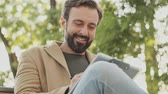park : View from below of Smiling elegant bearded man in coat writing something in clipboard and yawning while sitting in the park outdoors Stock Footage