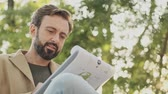 yetişkinler : Pleased elegant bearded man in coat reading documents in clipboard while sitting in the park outdoors Stok Video