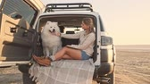 A nice young woman is petting a dog while reading a book in the trunk outdoors in summer. The camera moves away