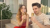 An attractive couple is drinking champagne while sitting on the stairs outside in the garden Archivo de Video