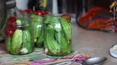 konserve : A woman pours hot marinade cucumbers and tomatoes placed in a jar. Pickling cucumbers and tomatoes. Cucumbers, tomatoes and spices packed in glass jars. Video shot camera Canon 70D. Stok Video