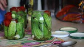 przetwory : Woman covers covers banks, pickles cucumbers. Pickling cucumbers and tomatoes. Cucumbers, tomatoes and spices packed in glass jars. Video shot camera Canon 70D.