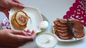 taze : The woman adds sour cream to the pancakes lying on the plate. Preparation of pancakes.