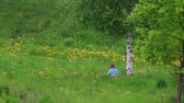 A woman sits in a meadow among the flowers near the birch tree and rests.
