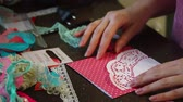 The girl is engaged in making greeting cards at home. Using paper, lace, braid and other materials.
