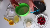 confeitaria : The woman stirs the dough. Next to the table are ingredients for pie Stock Footage