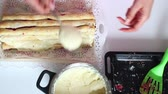 chef quipe : The woman lubricates the cream with a folded biscuit sticks with stuffing. The process of making a cake Pile. All stages of preparation. Stock Footage