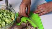 Russian meat salad with vegetables and mayonnaise. A woman cuts off a baked meat for a salad. Vídeos