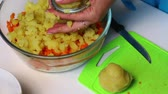majonéza : Russian meat salad with vegetables and mayonnaise. A woman is cutting boiled potatoes.