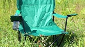 kemping : A picnic chair stands on a light-flooded meadow. Herbs and flowers sway from the summer wind.