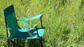kempování : A picnic chair stands on a light-flooded meadow. Herbs and flowers sway from the summer wind.