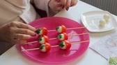 codorna : Kebabs from quail eggs and tomatoes on wooden skewers in the shape of mushrooms. Stock Footage