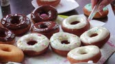 A woman decorates with dressing American donuts glazed with melted chocolate. Vidéos Libres De Droits