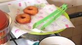 A woman is cooking American donuts. Bake them in sunflower oil. Nearby are cooked donuts. Vidéos Libres De Droits