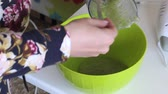 The woman puts in a container applesauce mashed with mint leaves. For making marshmallow.