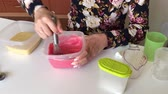 deser : A woman adds a drop of dye in the batter and mixes. Wideo