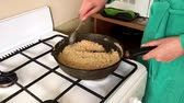 biscoitos : A woman fry biscuit crumbs in a frying pan. For the preparation of dessert.