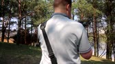 草の : A young man shoots video on a smartphone in spring park. Uses electronic gimbal.
