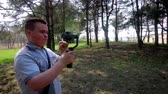 lawns : A young man shoots video on a smartphone in spring park. Uses electronic gimbal.