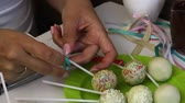 deegrol : Woman decorates pop cake. Tie a bow from a braid on a stick.