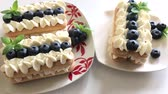 mascarpone : Cakes made of savoyardi cookies and cream. Decorated with blueberries and mint. Lie on the plates..mov