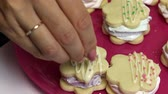 kek : Making a marshmallow sandwich. A woman sprinkles decorative chocolate cookies. Straightens her hand. Stok Video