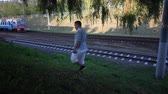 холеный : A young man walks along the railway tracks. A commuter train moves past.