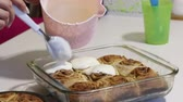 ロールパン : A woman is applying glaze on baked cinnabons. Rosy buns are on baking sheets.