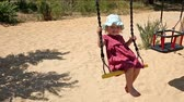 facial : Little girl riding on a swing sunny summer day. The concept of a happy childhood.