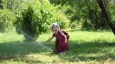 drench : Little girl watering Sprinkle with hot sunny summer day in the park. The concept of carefree childhood.