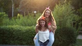 Cheerful girlfriend meet in park. Girl holds the girlfriend on piggyback. The concept of true friendship.