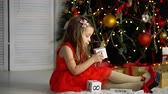 Nice little girl in a red dress and shoes sits next to a Christmas tree and plays with blocks. Happy childhood.