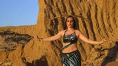 Oriental beauty dancing belly dance with a sword. Delightful and alluring grace of movements. Girl dancing in the desert. She is balancing a sword on her head.