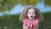 Little curly cute girl eating red apple outdoors. She enjoys a taste of ripe fruit. Stok Video