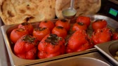 The cook is baking the baked tomatoes on a plate. Stock mozgókép