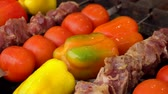 Meat, bell peppers, and tomatoes are rotated on the grill Stock mozgókép