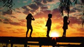 Sunset and silhouettes of happy kids jumping on the wooden pier above the lake water Wideo