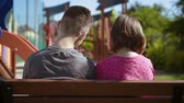 irmãs : Back view of a couple teenage - teen boy and girl sitting together on the bench outdoors. Friendship and love concept - close-up. Stock Footage