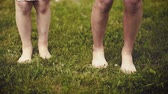 sepia : Slow motion shot of bare feet of little girls walking, jumping and running on green grass. Happy children playing outdoors in spring or summer park. Fun at field - retro.