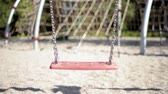 abduction : Abandoned empty swings swaying in the wind at children playground outdoors