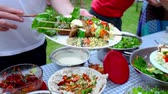 Close up on a man filling his plate with an outdoor potluck (Package of 2 scenes, panning left, panning right)