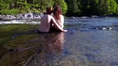 riverbank : Young couple in love, sitting side by side in a shallow river flowing on a beautiful sunny day