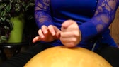 hand drum : Close up scene of a woman dressed in blue playing calabash percussion over african music