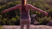 Girl standing up and raising her hands while looking at the horizon on a mountain with rock cliffs at sunset - Traveling up from behind her