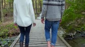 Couple walking in a forest, crossing a bridge and holding hands