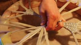アーティファクト : Hands of an artisan making sacred drum. Close up footage of a skilled worker using vintage methods to create a sacred drum. Freshly dyed membrane is seen knotted on the back of the membranophone. 動画素材